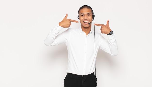 Jeune homme noir souriant avec confiance en montrant son large sourire, attitude positive, détendue et satisfaite