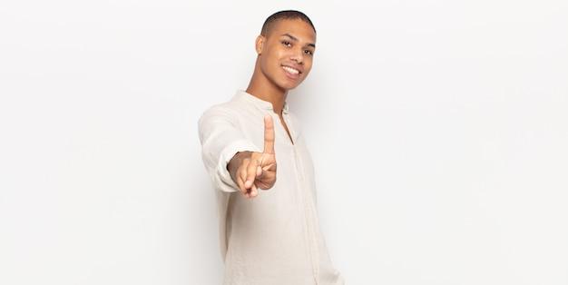 Jeune homme noir souriant fièrement et avec confiance en faisant le numéro un pose triomphalement, se sentant comme un leader