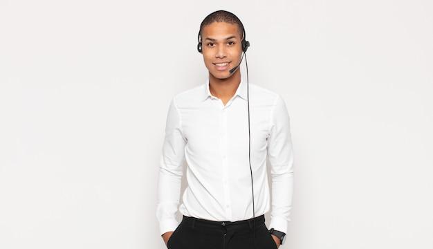 Jeune homme noir souriant joyeusement avec une main sur la hanche et une attitude confiante, positive, fière et amicale