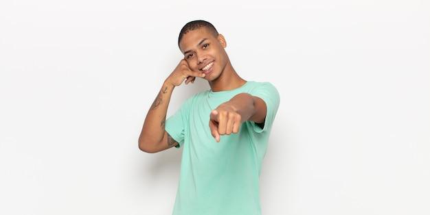 Jeune homme noir souriant joyeusement et pointant tout en faisant un appel, vous geste plus tard, parler au téléphone