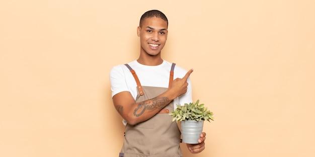 Jeune homme noir souriant joyeusement, se sentant heureux et pointant vers le côté et vers le haut, montrant l'objet dans l'espace de copie