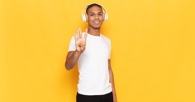 Jeune homme noir souriant et à la recherche amicale, montrant le numéro quatre ou quatrième avec la main en avant, compte à rebours