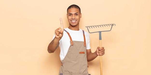Jeune homme noir souriant et à la sympathique, montrant le numéro un ou d'abord avec la main en avant, compte à rebours