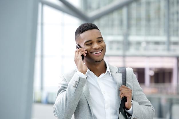 Jeune homme noir souriant avec téléphone portable