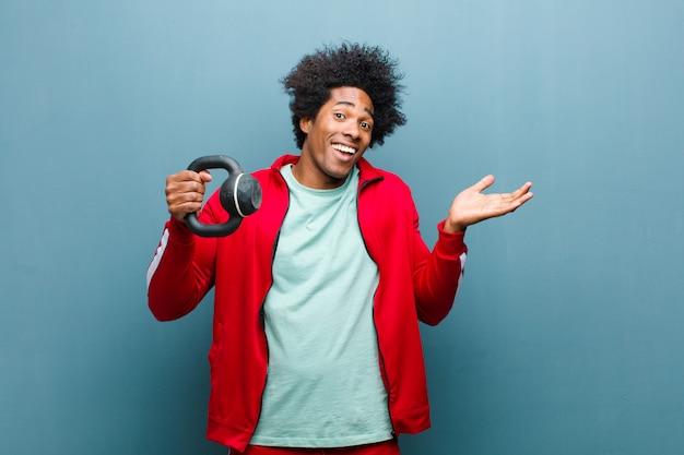 Jeune homme noir sport homme avec un haltère contre bleu grunge w