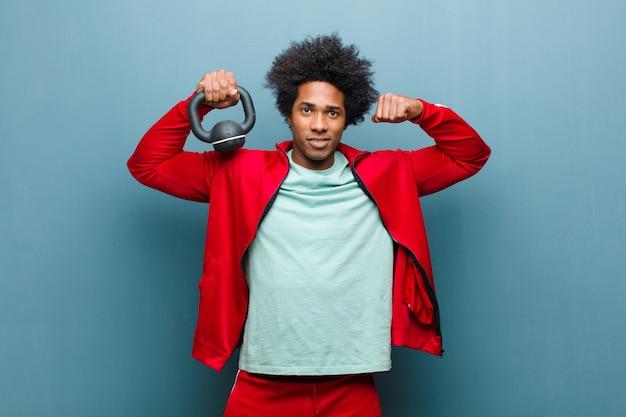 Jeune homme noir sportif avec un haltère bleu grunge