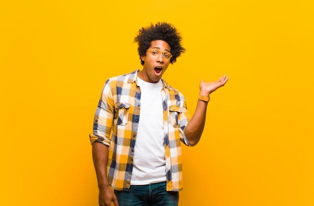 Jeune homme noir à la surprise et choqué, avec la mâchoire tombée tenant un objet avec une main ouverte sur le côté contre le mur orange