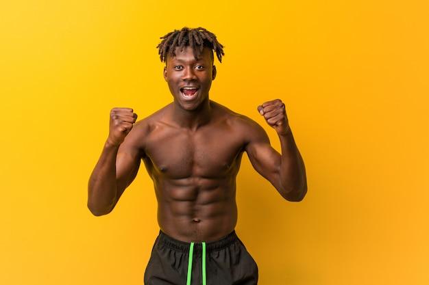Jeune homme noir torse nu portant maillot de bain acclamant insouciant et excité. concept de victoire.