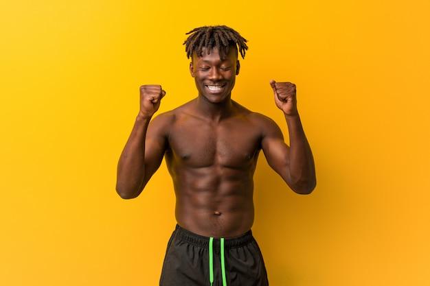 Jeune homme noir torse nu portant un maillot de bain levant le poing, se sentant heureux et réussi. concept de victoire.