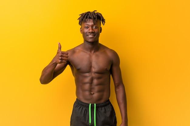 Jeune homme noir torse nu porte maillot de bain souriant et levant le pouce vers le haut