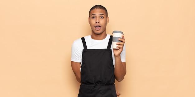 Jeune homme noir à la très choqué ou surpris, regardant la bouche ouverte en disant wow