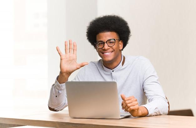 Jeune homme noir utilisant son ordinateur portable montrant le numéro cinq