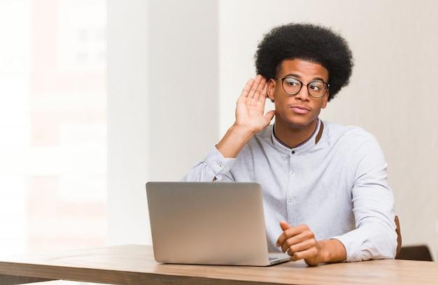Jeune homme noir utilisant son ordinateur portable pour écouter un commérage