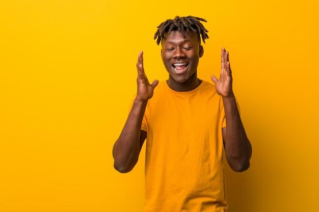 Jeune homme noir vêtu de dreads joyeux rire beaucoup. notion de bonheur.