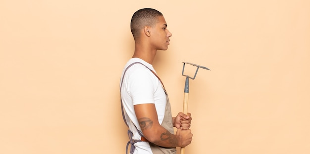Jeune homme noir sur la vue de profil à la recherche de copier l'espace à venir, penser, imaginer ou rêver