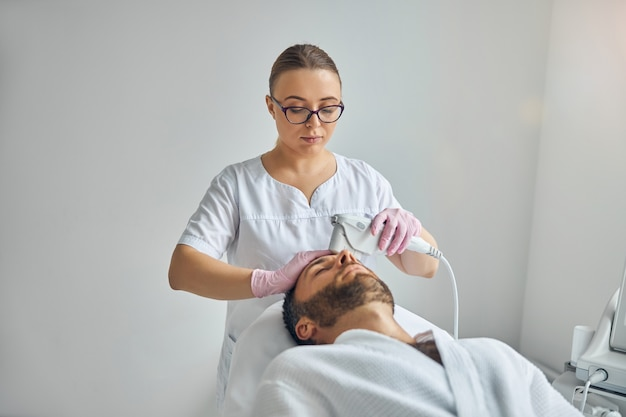 Jeune homme non rasé allongé sur un lit de repos tout en recevant un traitement facial au laser dans une clinique cosmétologique