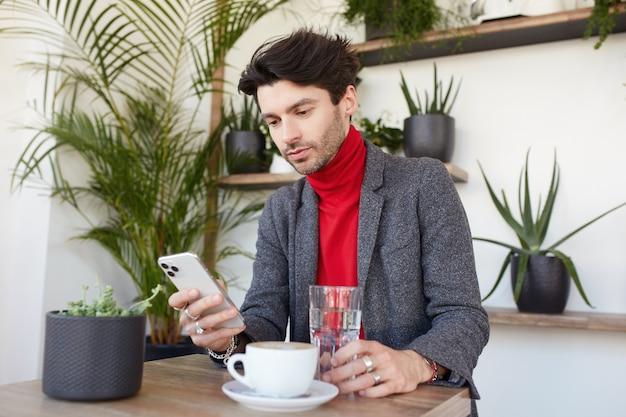 Jeune homme non rasé aux cheveux bruns attrayants assis dans un café