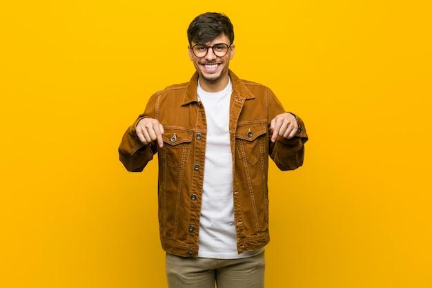 Jeune homme occasionnel hispanique pointe avec les doigts, sentiment positif.