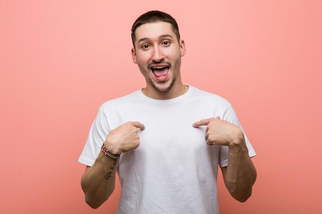 Jeune homme occasionnel surpris se montrant du doigt, souriant largement.