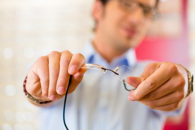 Jeune homme à l'opticien avec des lunettes