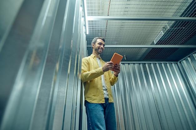 Jeune homme optimiste regardant la tablette dans le garage