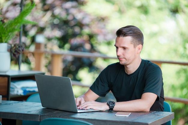 Jeune homme avec ordinateur portable au café en plein air, boire du café. homme utilisant un smartphone mobile.