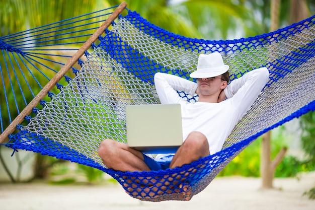 Jeune homme avec un ordinateur portable au hamac sur la plage blanche