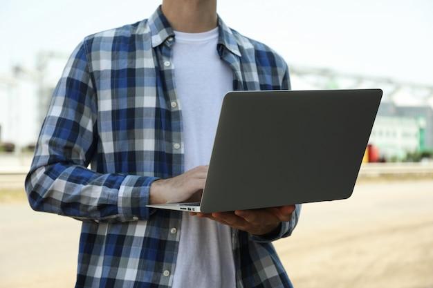 Jeune homme avec ordinateur portable contre les silos à grains. entreprise agricole