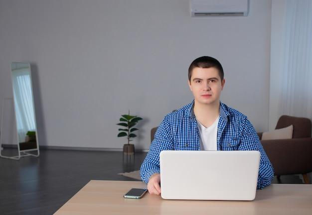 Jeune homme avec ordinateur portable est assis à un bureau dans le bureau. testeur ou concepteur web au travail