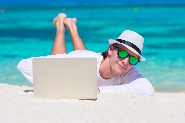 Jeune homme avec un ordinateur portable sur une plage tropicale