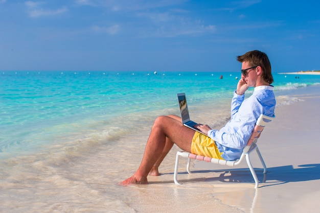 Jeune homme avec ordinateur portable et téléphone portable sur la plage tropicale