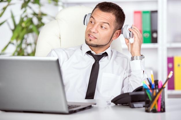 Jeune homme avec ordinateur portable, téléphone à la table.