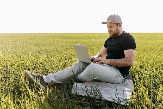 Jeune homme avec un ordinateur portable travaillant, assis dans un champ avec de l'herbe verte fraîche.