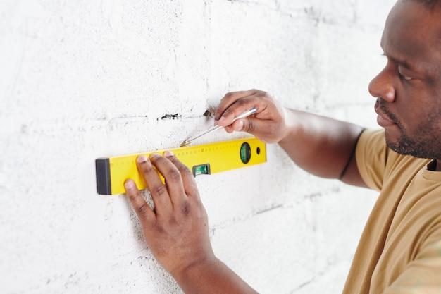 Jeune homme d'origine africaine avec une ligne de dessin au crayon sur un mur de briques peintes en blanc lors de l'utilisation d'un outil à main de mesure de niveau pendant la rénovation domiciliaire