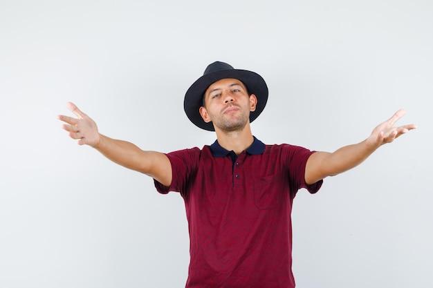 Jeune homme ouvrant les bras pour un câlin en t-shirt, chapeau et ayant l'air gentil. vue de face.