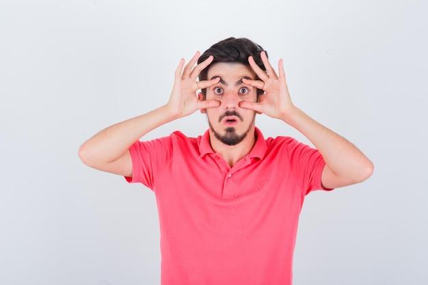 Jeune homme ouvrant les yeux avec les mains en t-shirt rose et l'air anxieux. vue de face.