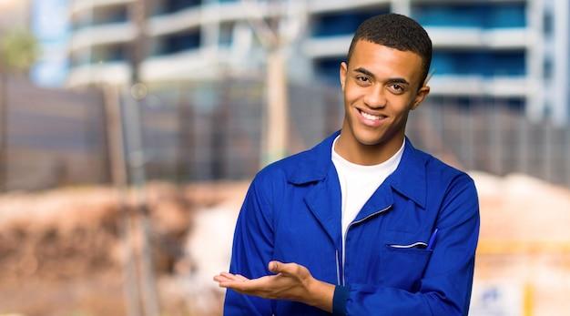 Jeune homme ouvrier américain présentant une idée tout en regardant souriant vers un chantier de construction