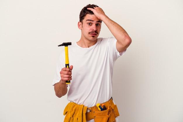 Jeune homme ouvrier caucasien avec des outils isolés sur fond blanc étant choqué, elle s'est souvenue d'une réunion importante.