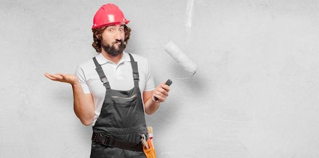 Jeune homme ouvrier avec un rouleau à peinture