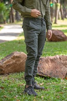 Jeune homme en pantalon vert debout dans le parc