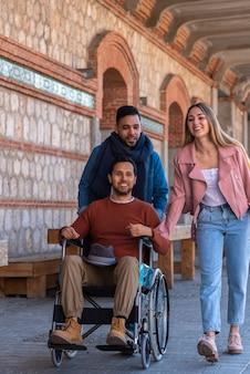 Jeune homme paralysé dans un fauteuil roulant accompagné d'un jeune homme et d'une fille se promenant