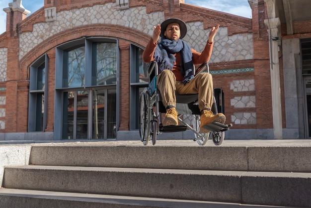 Jeune homme paralysé dans un fauteuil roulant frustré devant certains escaliers