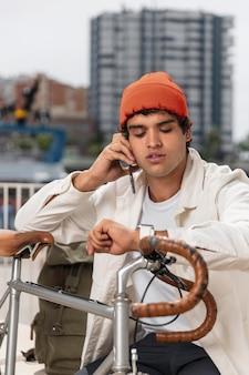 Jeune homme parlant au téléphone à côté de son vélo