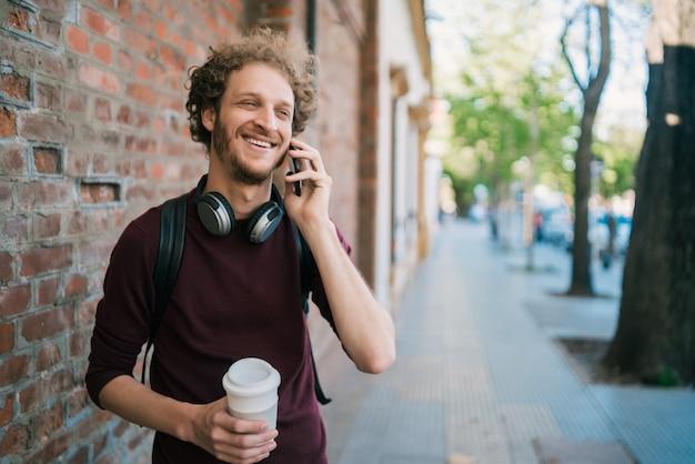 Jeune homme parlant au téléphone à l'extérieur.
