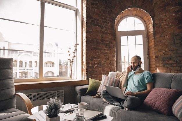 Jeune homme parlant au téléphone à la maison tout en travaillant