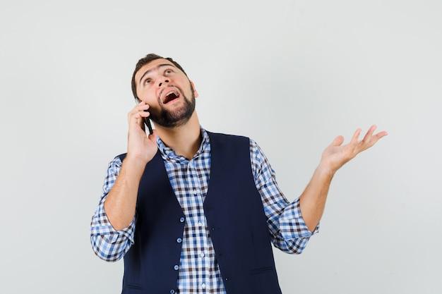 Jeune homme parlant au téléphone mobile en chemise, gilet et à la confusion.