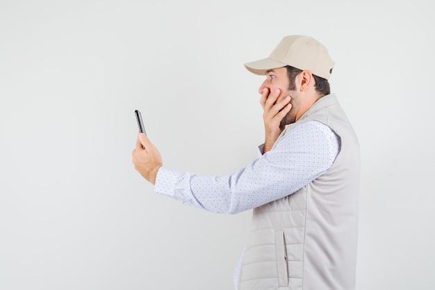 Jeune homme parlant à quelqu'un via un appel vidéo et couvrant la bouche avec la main dans une veste beige et une casquette et à la surprise. vue de face.