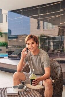 Jeune homme parlant sur son téléphone portable au bord de la piscine