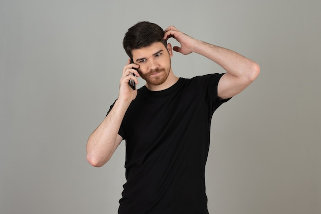 Jeune homme parlant avec téléphone sur un gris.