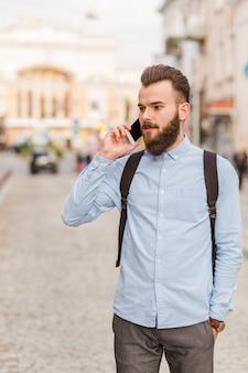 Jeune homme parlant sur un téléphone mobile